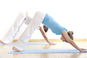 Art of Living Yogagruppe bei der Asana herabschauender Hund, die dabei hilft innere Ruhe und Kraft zu finden..