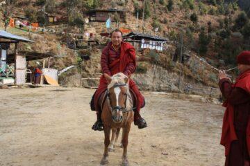 Bhutanesischer Mönch auf dem Rücken eines Pferdes