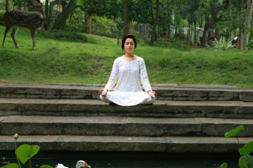 Meditierende Frau im Garten des Sri Sri Panchkarma-Zentrums in Bangalore