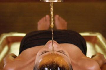 Frau beim entspannenden Stirnölguss Shirodhara