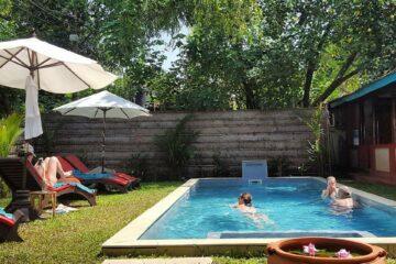 Leute baden im Pool im Garten unter Bäumen