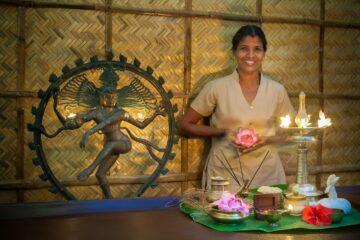 Lächelnde Inderin steht vor Tablett mit ayurvedischen Zubehör für Behandlung