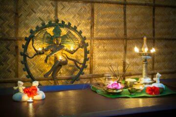 Von Kerzen beleuchtete goldene Götterstatue an der Wand
