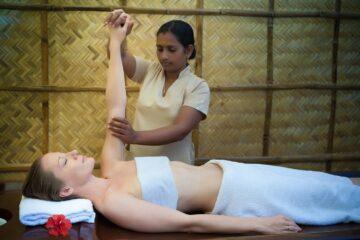 Inderin hält sanft den Arm ihrer Klientin in die Höhe