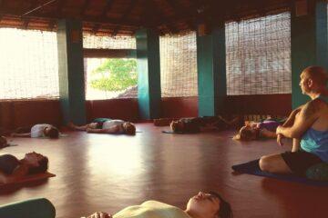 Menschen liegen und sitzen auf Yogamatten