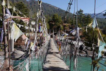 Brücke mit Gebetsfahnen in Bumthang mit Bergen im Hintergrund