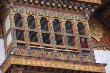 Lachender Mönch im Fenster eines Klosters in Dzong Punakha