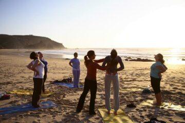 Gruppe beim Yoga am Strand