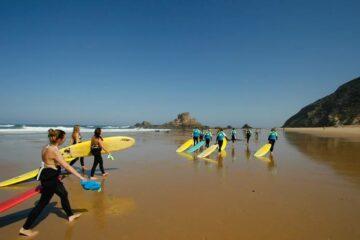 Gruppe mit Surfboard am Strand