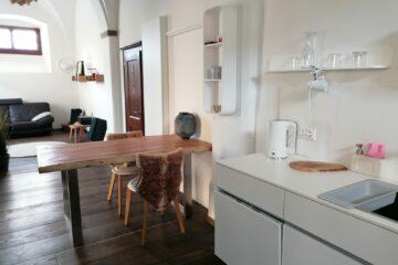 Rustikaler Holztisch im Übergang von Küche zum Wohnbereich