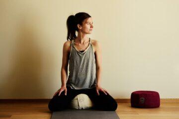 Frau auf Yogakissen