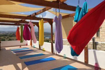 Dachterrasse an deren Dachbalken bunte Aerial-Yoga-Tücher über blauen Yogamatten aufgereiht sind