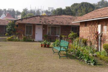 Grüne Bank vor einem Bungalows des Swati Rama Sadhaka Grant Ashram