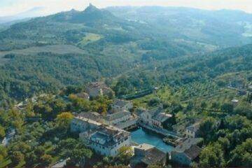 Blick von oben auf Bagno Vignoni umgeben von grünen Hügeln