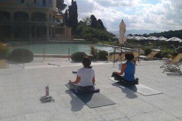 Teilnehmer im Lotussitz auf Yoga-Matten vor dem Hotelpool