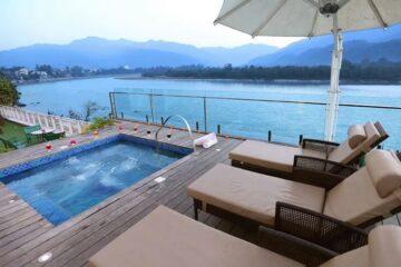 Pool mit Blick auf Ganges und die dahinterliegende Berge in Rishikesh