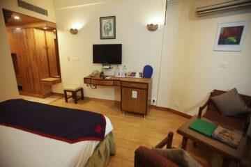 Kommode und Flachbildfernseher an Wand und Sitzgelegenheit aus Holz in Superior-Zimmer in Rishikesh