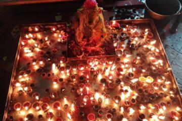 Kerzenmeer flankiert Götterstatue in der Mitte