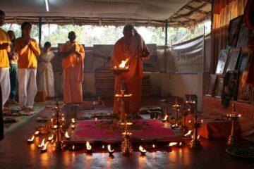 Mönche zelebrieren Ritual mit entzündeter Flamme vor goldenen Kandelabern im Kreis