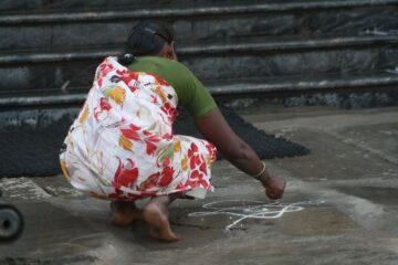 Frau in Sari kniet auf Straße und malt mit Kreide ein Symbol auf den Weg