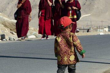 Gruppe von Nonnen in roter Tracht begegnen einem kleinen Jungen mit Mütze auf der Straße in Ladakh