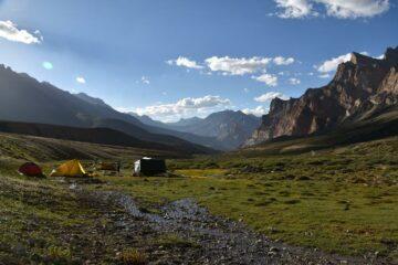Zelte auf grünem Plateau inmitten Bergkulisse Ladakhs