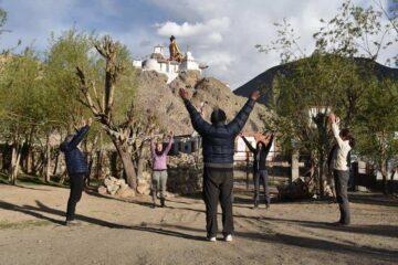 Yogaübung am Fuße eines Bergklosters mit Jacken