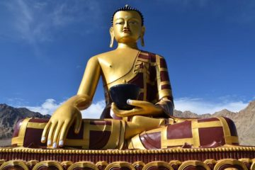 Goldene Buddha-Statue vor blauem Himmel