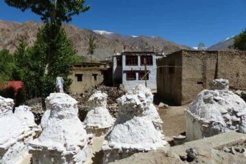 weiße Steinskulpturen vor Bergdorf in Ladakh