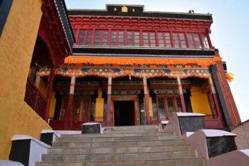 Blick auf Eingang orange-rote Säulenfassade eines Klosters im Himalaya