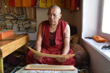 Mönch mit Brille liest von einem Papier