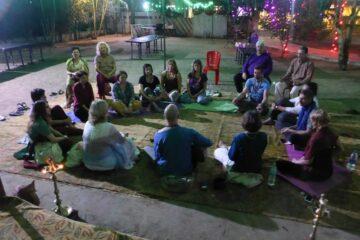 Johannes Vogt sitzt mit Kunden im Kreis auf dem Boden