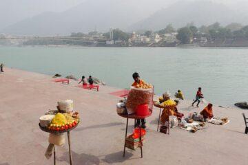 runder Verkaufstisch mit Opfergaben und Menschen am Ufer des Ganges