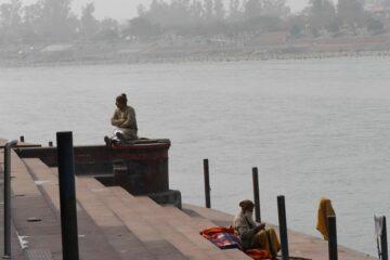 Sitzende Menschen an den Treppenstufen zum Ganges