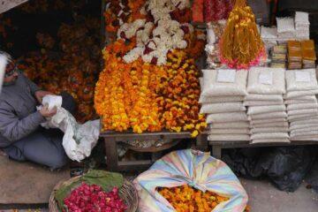 Dunkelgelbe Blüten und Ketten als einem Marktstand in Nordindien