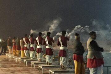 Männer räuchern in Richtung des Ganges beim Abendaarti in Rishikesh