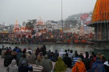 Menschen sitzen am Ganges beim Parmarth Niketan Ashram