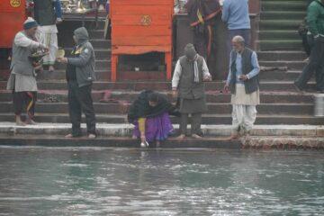 Frau schöpft Wasser aus dem Ganges