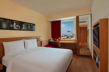Doppelbett und Tisch vor Fenster mit rotem Vorhang in Hotel in Delhi
