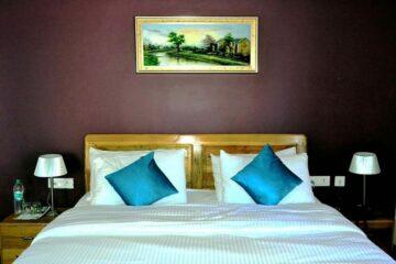 Bett mit türkischen Kissen in Hotel in Binsar