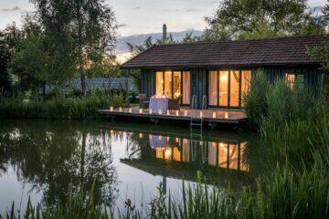 Innen beleuchtetes Haus mit Terrasse am See bei Kerzenschein