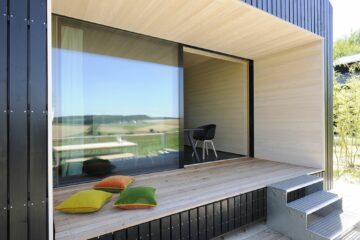 Holzsitzbank mit Kissen auf Terrasse
