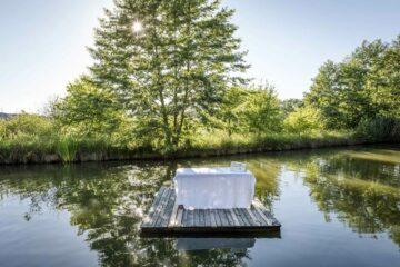 Weiß betuchte Wellnessliege auf einem Holzstück mitten auf dem Wasser