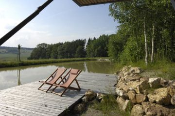 Zwei Liegestühle am Steg direkt am Wasser
