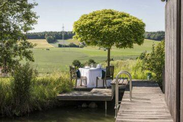 Einsamer Tisch für zwei auf Steg im Grünen