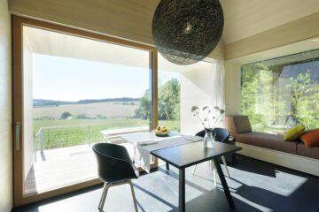Tisch und Sofa vor Fenster auf Terrasse