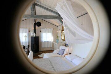 Blick durch Bullaugenfenster auf Schlafzimmer