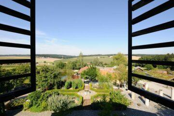Blick durch das geöffnete Fenster auf den grünen Innenhof