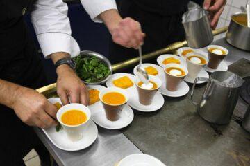 Suppen in Schalen werden von Hand garniert