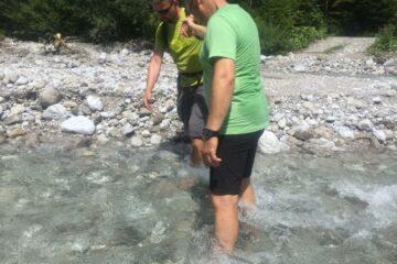 Mann hilft Frau durch den Wildbach